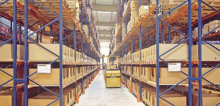 Operário trabalhando num corredor entre estantes convencionais