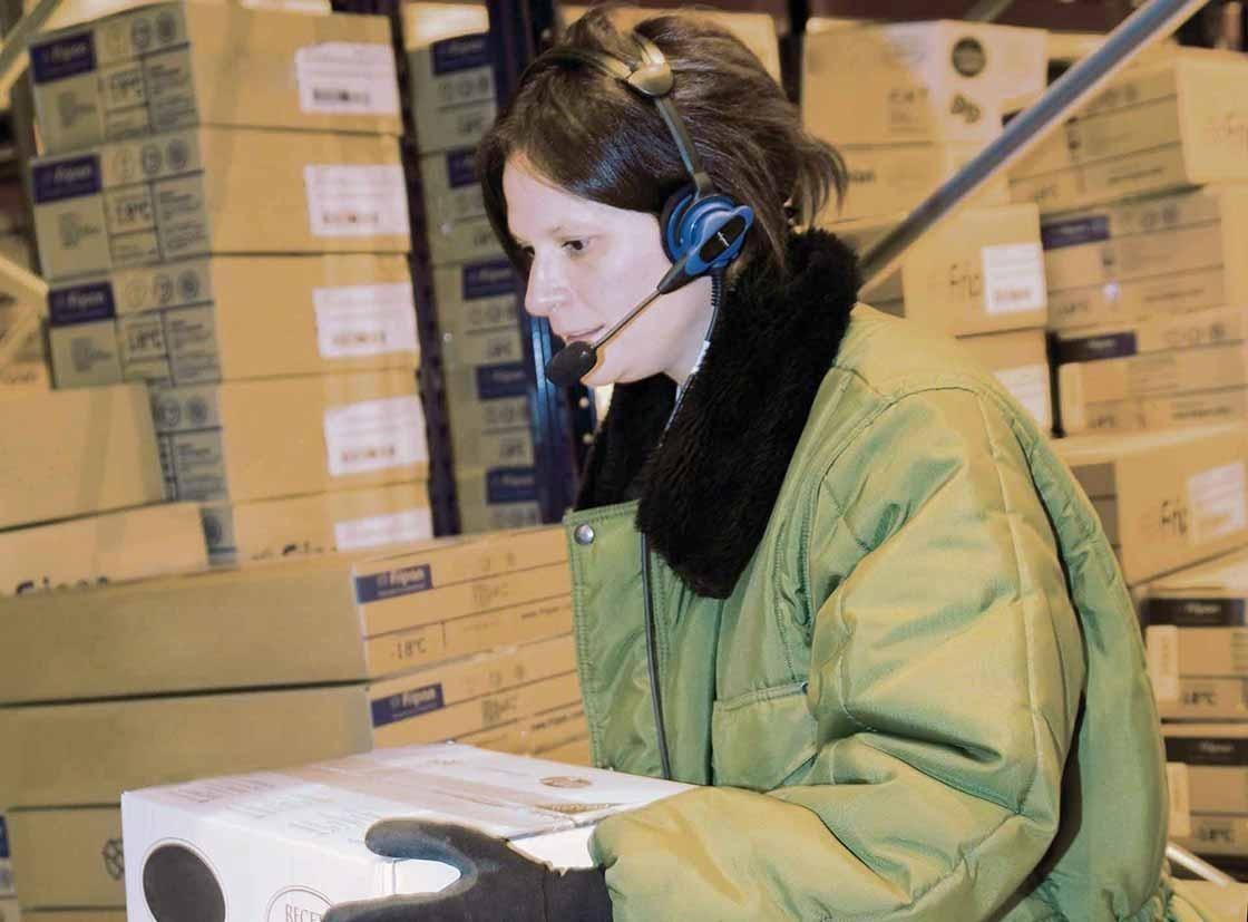 Um operador realiza as tarefas de preparação de pedidos com um sistema de voice picking
