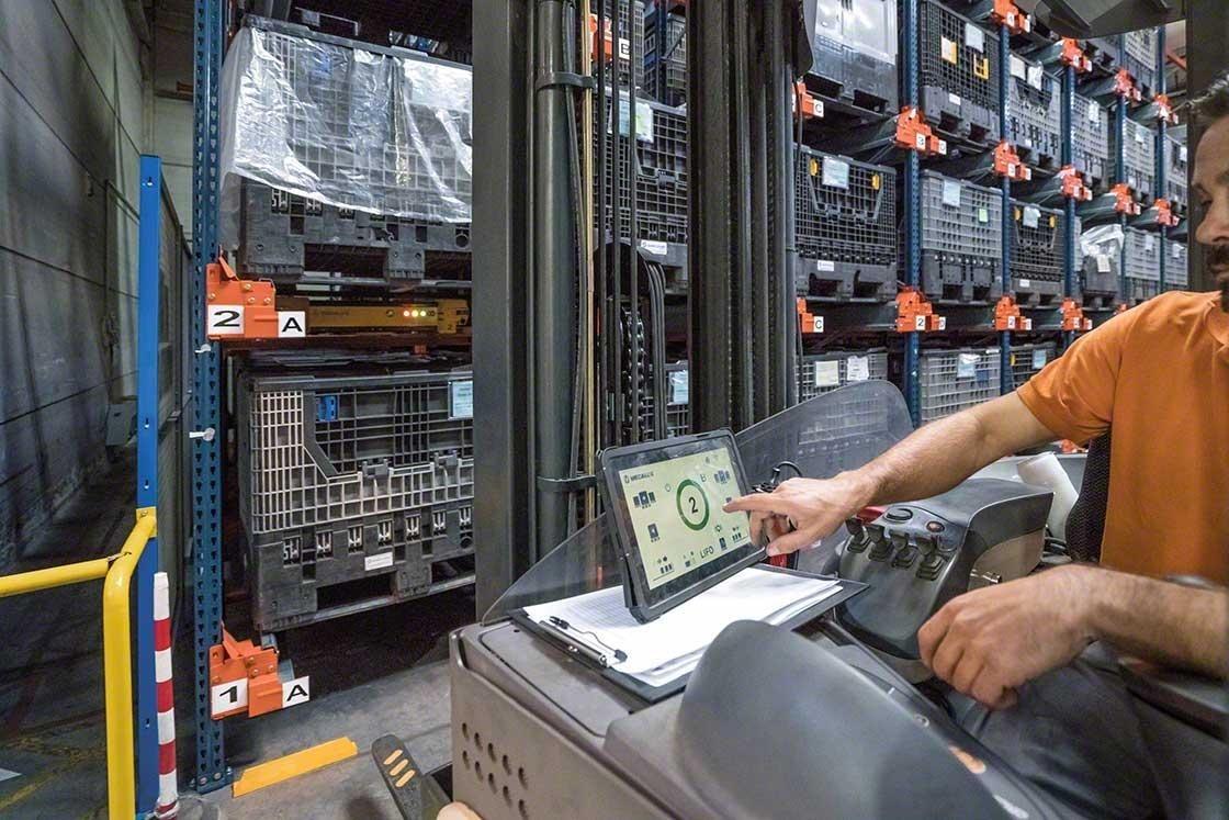 Um operador manuseia o Pallet Shuttle a partir do empilhador com um tablet digital em um armazém robotizado